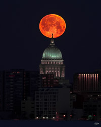 the full moon sets over the Wisconsin State Capitol, in Madison