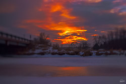 the orange glow of sunset through clouds from where I lay, belly to the ground, on the edge of the frozen river.